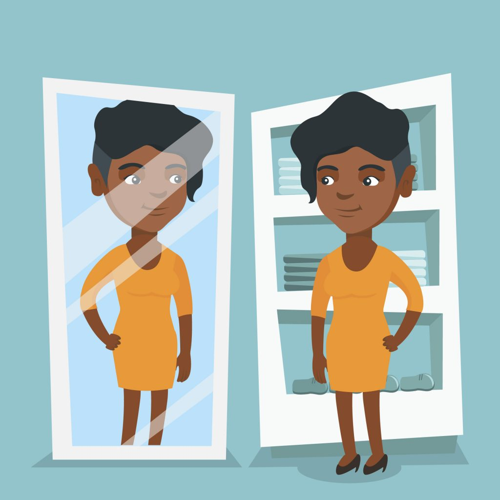 A young African-American woman is looking at her reflection in the mirror.