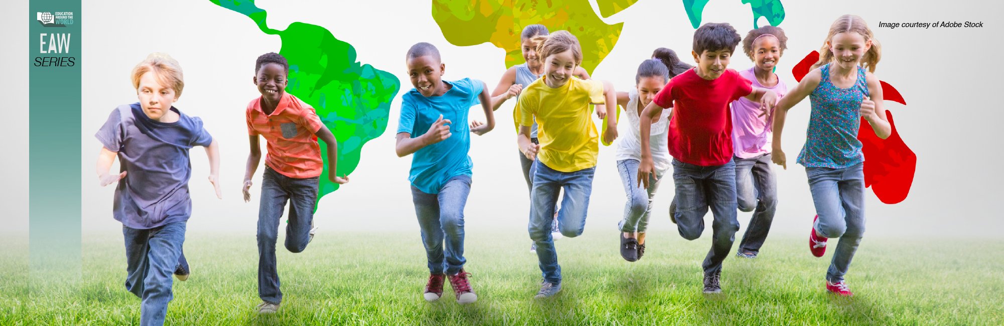 A group of kids is running on the grass; behind them is a colorful mural of the world map.