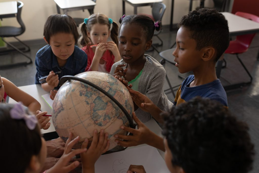 A diverse group of young students is looking at the globe.