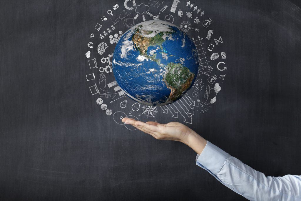 A photo of a globe hovering above the open hand with a chalkboard in the background.
