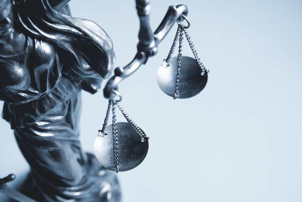 Picture of a Lady Justice. Greyscale cropped view of the scales of justice on a small metal statue with copy space in a concept of law enforcement and the judiciary