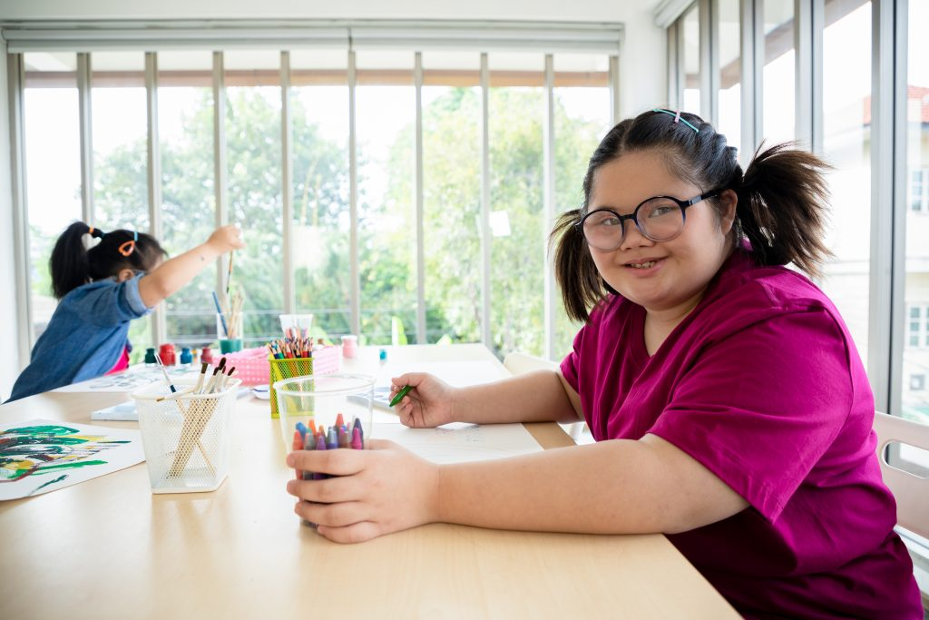 A girl with Down syndrome is sitting at her desk and working on the sketch.