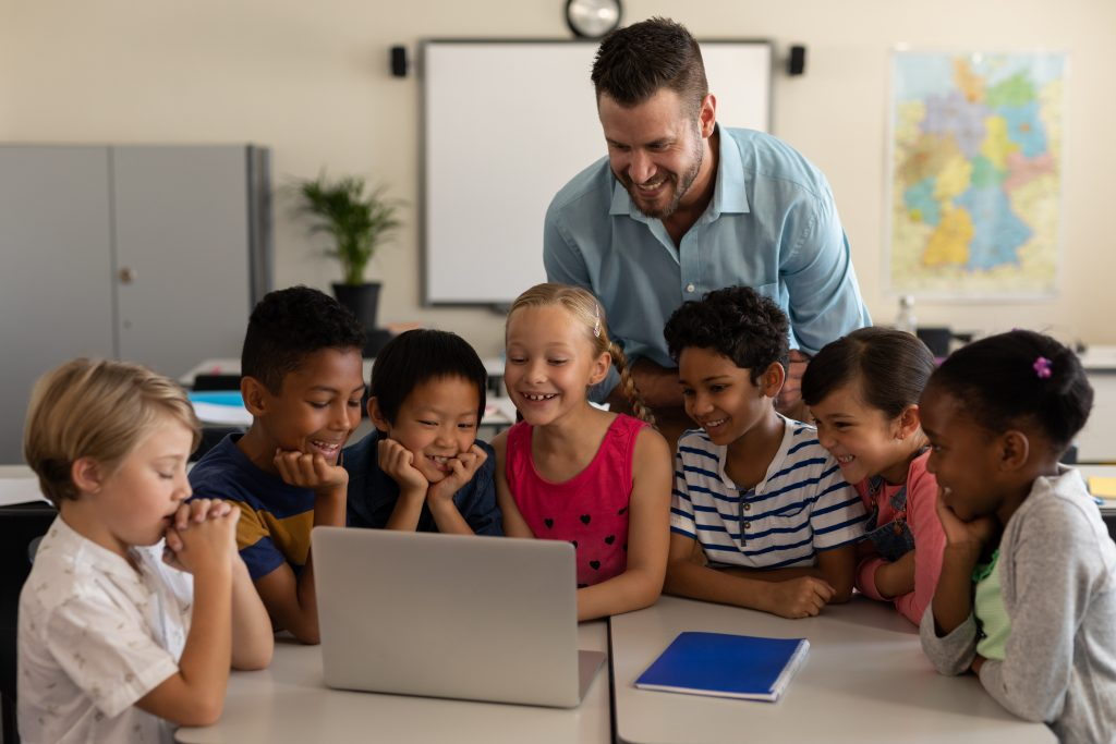Male teacher with a diverse group of young students.