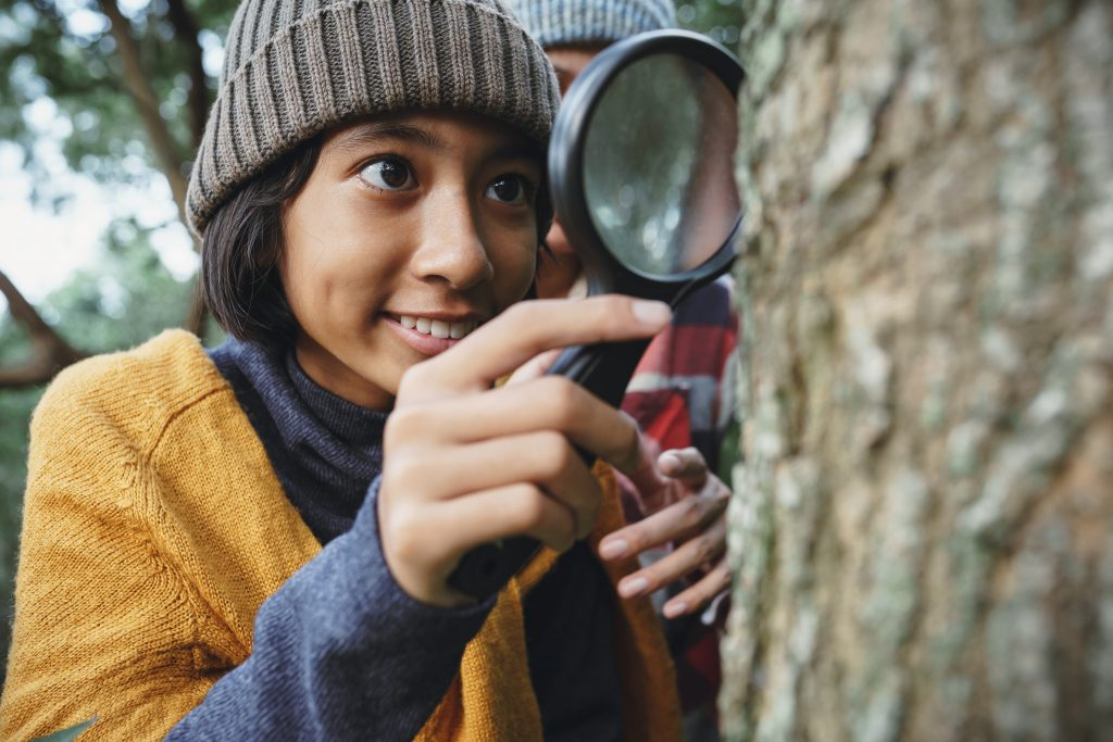 Asian teenage girl is examining the tree trunk through a magnifying glass.