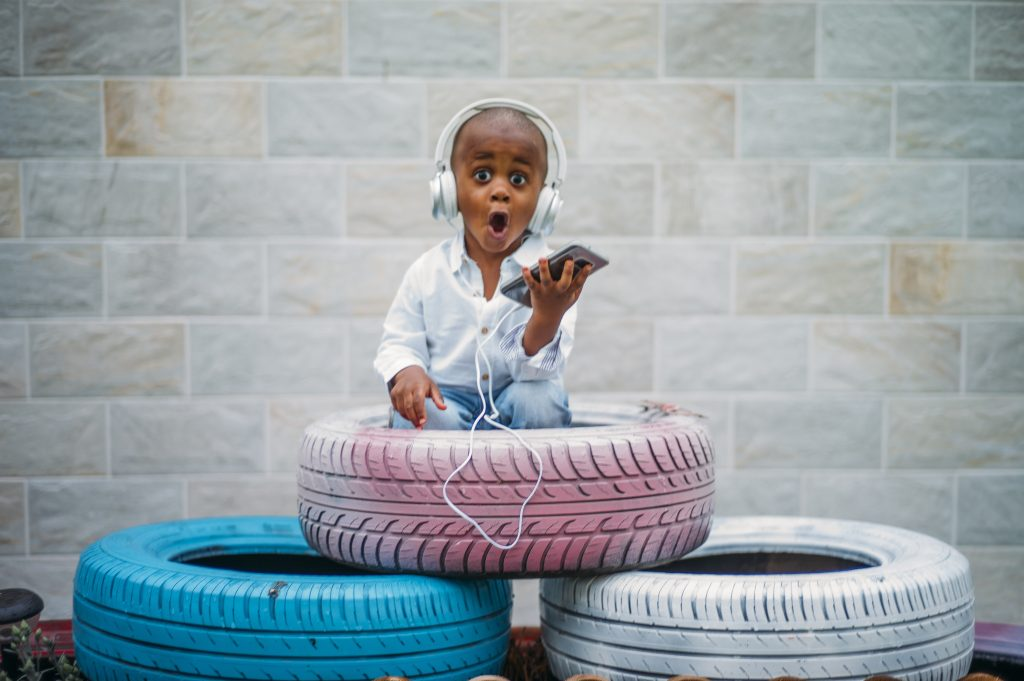 A child sitting in a pile of tires and listening to the music on the headphones.