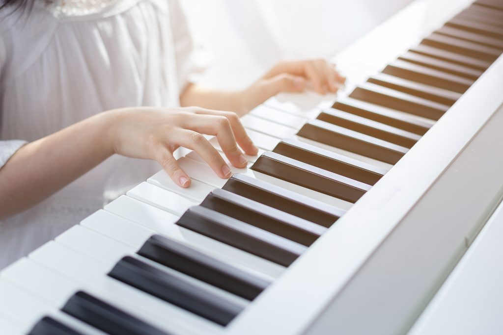 A picture containing close up of a piano keys with human hands touching them while playing a melody.