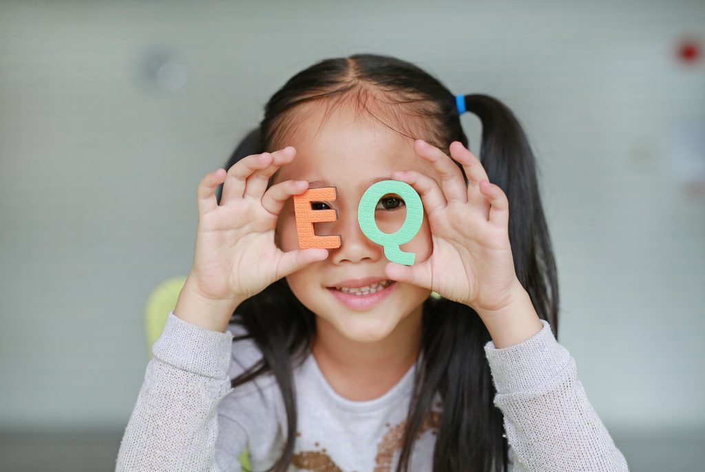 A little Asian child girl holding alphabet EQ (Emotional Quotient) text on her face. Education and development concept.