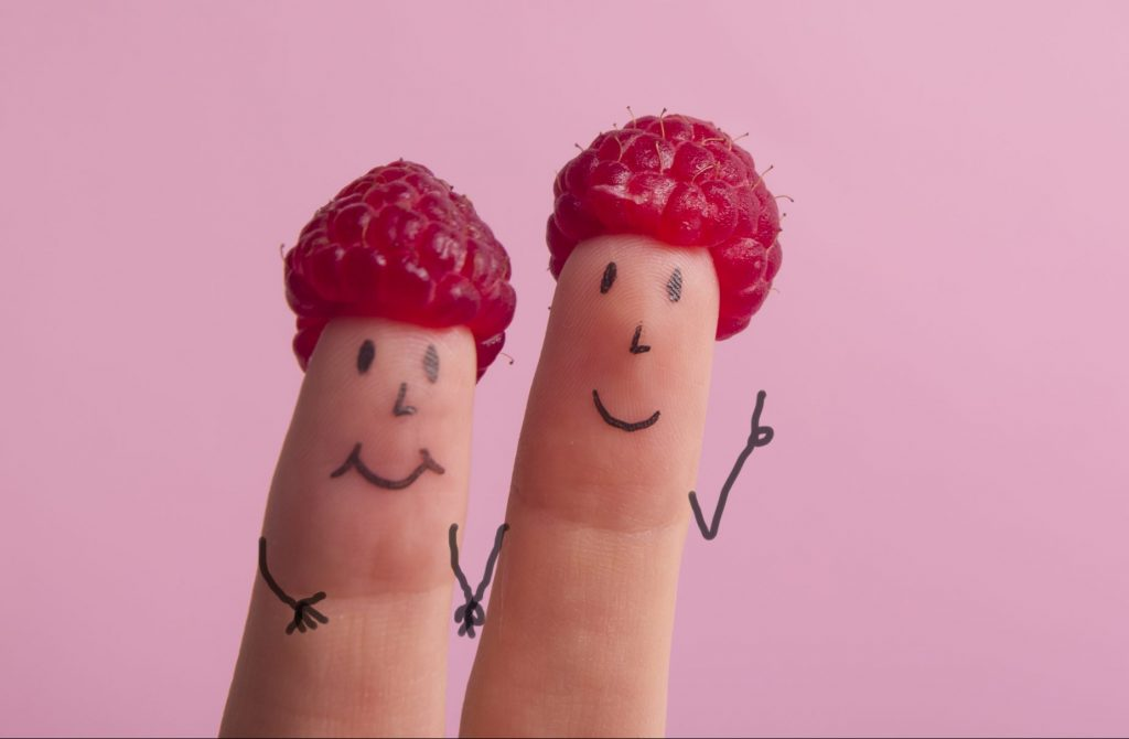 Two fingers with painted faces and raspberry hats.