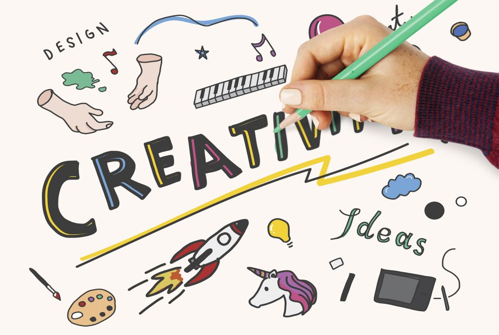 A person, hand showing only, is drawing on the creativity board.
